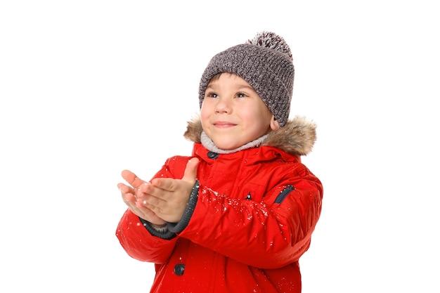 Netter kleiner junge in warmer kleidung, der mit schnee spielt