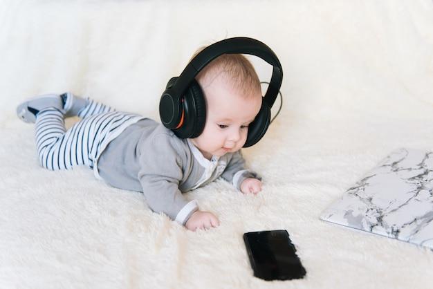 Netter kleiner junge liegt in kopfhörern auf dem bauch und schaut in laptop