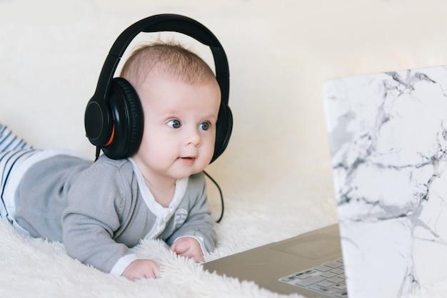 Netter kleiner junge liegt in kopfhörern und schaut in laptop