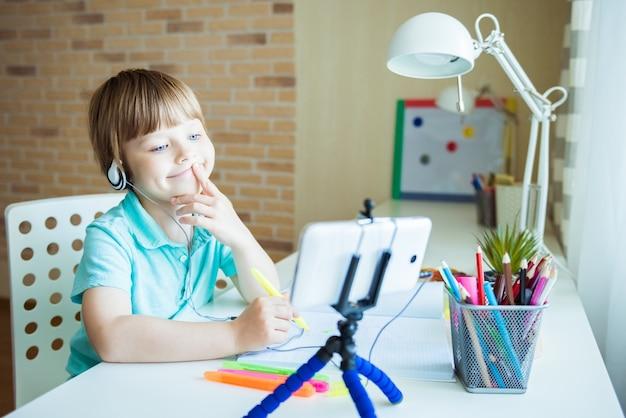 Netter kleiner junge malt mit farbstiften zu hause, im kindergarten oder in der vorschule. kreative spiele für kinder, die zu hause bleiben