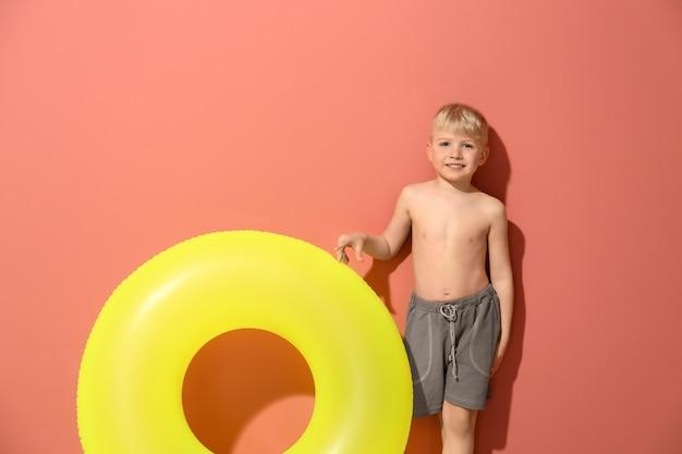 Netter kleiner junge mit aufblasbarem ring auf farbe