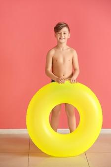 Netter kleiner junge mit aufblasbarem ring nahe farbwand