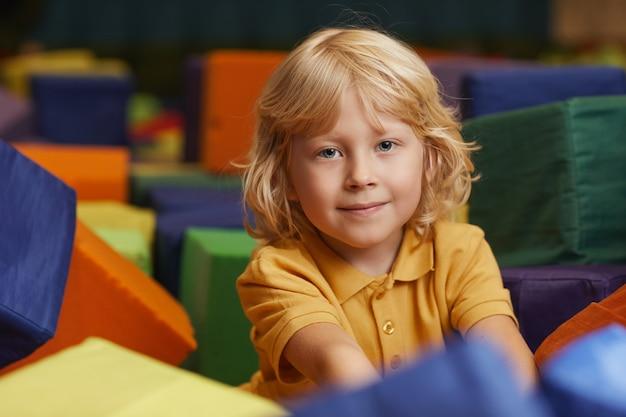Netter kleiner junge mit blondem haar, das vorne schaut, während mit großen farbigen würfeln im park spielt
