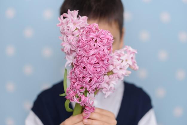 Netter kleiner junge mit blumenstrauß der rosa blumen als geschenk.