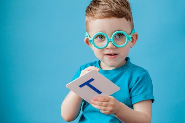 Netter kleiner junge mit brief auf hintergrund. kind lernt briefe. alphabet