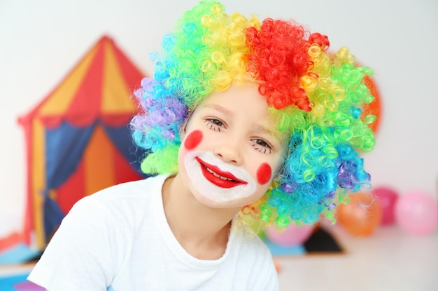 Netter kleiner junge mit clown-make-up in regenbogenperücke drinnen. feier zum aprilscherz