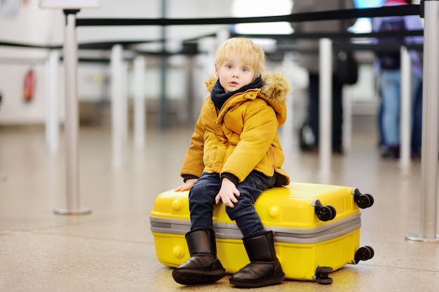 Netter kleiner junge mit großem gelbem koffer am internationalen flughafen vor flug