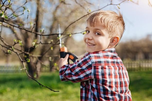 Netter kleiner junge mit haselnussbraunen augen, der seiner familie in einem garten hilft, nach vorne schaut und lächelt