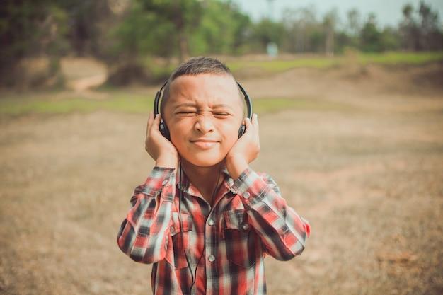 Netter kleiner junge mit kopfhörer für das hören im park, ihr gesicht fühlen sich wie glücklich mit sonnenschein. thema ist verschwommen.