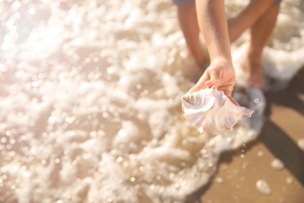 Netter kleiner junge mit muschel am strand