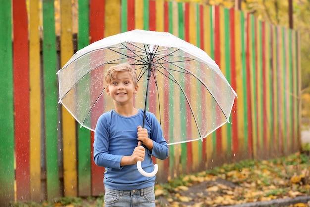 Netter kleiner junge mit regenschirm im herbstpark