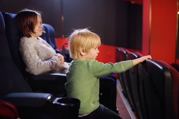 Netter kleiner junge mit seinem aufpassenden zeichentrickfilm der mutter im kino