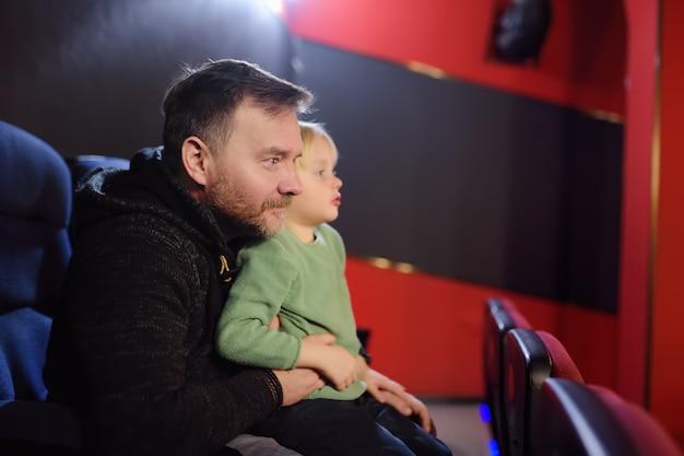 Netter kleiner junge mit seinem aufpassenden zeichentrickfilm des vaters im kino