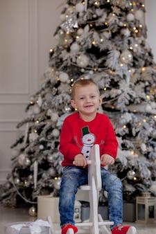 Netter kleiner junge mit weihnachtszubehör, das auf holzpferd vor weihnachtsbaum sitzt