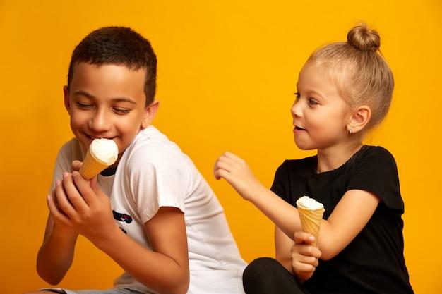 Netter kleiner junge möchte nicht eiscreme mit seiner schwester teilen. studioaufnahme auf einem gelben hintergrund
