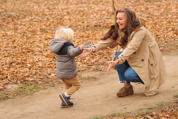 Netter kleiner junge rennt zu seiner mutter im herbstpark