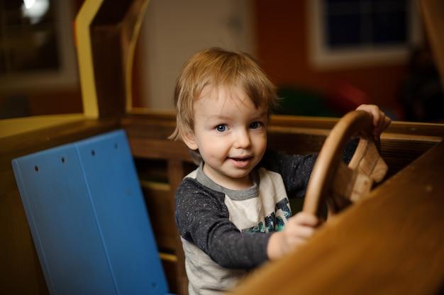 Netter kleiner junge spielt im hölzernen auto des spielzeugs