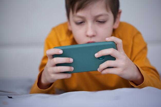 Netter kleiner junge spielt im videospiel auf seinem smartphone