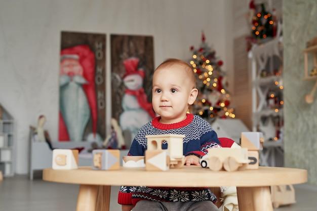 Netter kleiner junge spielt mit hölzernem zug, spielzeugauto, pyramide und würfeln des spielzeugs und lernt entwicklungskonzept. entwicklung der feinmotorik der kinder, fantasie und logisches denken
