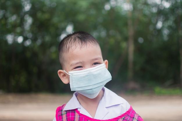 Netter kleiner junge tragen maske zum schutz coronavirus oder covid 19.