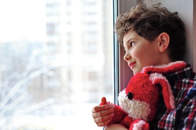 Netter kleiner junge umarmt sein spielzeug rotes kaninchen und schaut lächelnd aus dem fenster