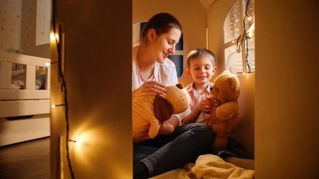 Netter kleiner junge und junge mutter, die nachts im zelt oder spielzeughaus spiele mit spielzeug-teddybären spielen. konzept des spielenden kindes und der familie, die nachts zeit zusammen haben.