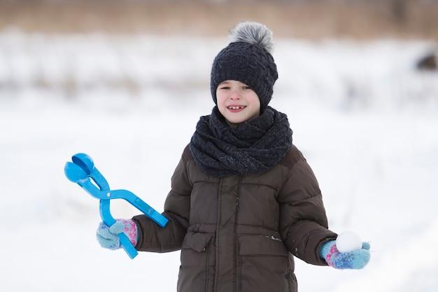 Netter kleiner junger lustiger zahnloser kinderjunge in der warmen kleidung, die spaß hat, schneebälle am kalten wintertag auf weißem hellem unscharfem kopienraumhintergrund zu machen. aktivitäten im freien, ferienspiele.