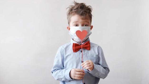 Netter kleiner kaukasischer junge in fliege mit rotem holzherz auf stock in schützender gesichtsmaske. valentinstag. covid.