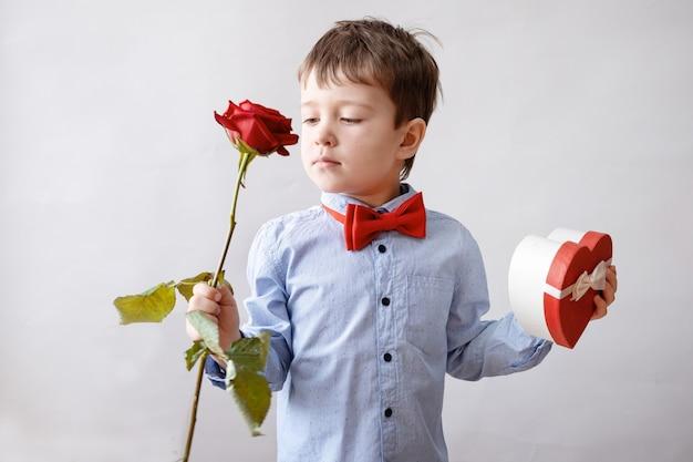 Netter kleiner kaukasischer junge in fliege mit roter herzgeschenkbox halten rose. valentinstag.