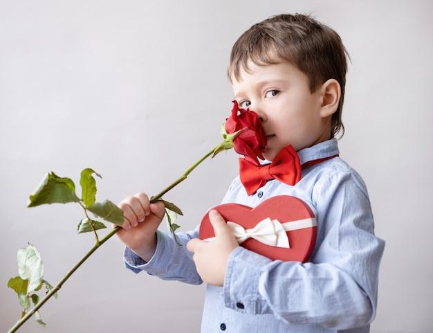 Netter kleiner kaukasischer junge in fliege mit roter herzgeschenkbox riechen rose. valentinstag.