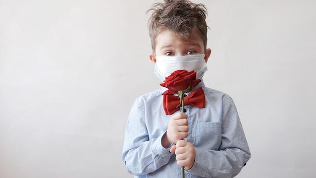 Netter kleiner kaukasischer junge in fliege mit roter rose in schützender gesichtsmaske. valentinstag. covid.