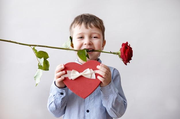 Netter kleiner kaukasischer junge in fliege mit weißem band der geschenkbox des roten herzens und rose im mund auf hellgrauem hintergrund. valentinstag.