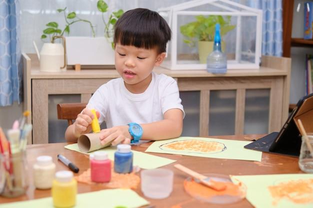 Netter kleiner kindergartenjunge genießt es, kleber zu verwenden, der zu hause kunst macht