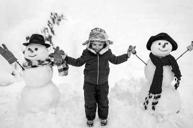 Netter kleiner kinderjunge auf schneebedecktem feld im freien. kinderjunge, der spaß im winterpark hat. winterkinder