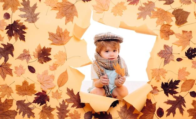 Netter kleiner kinderjunge, der blattgold auf gelbem hintergrund hält. verkauf für die gesamte herbstkollektion