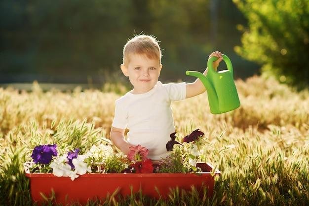 Netter kleiner kinderjunge, der blumensämlinge in einem topf im garten auf sonnenuntergang wässert. lustiger kleiner gärtner. frühlingskonzept, natur und pflege.