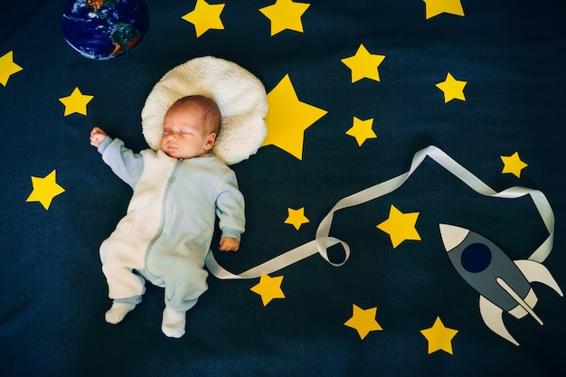 Netter kleiner kleinkindastronautenjunge, der im hintergrund des himmels mit einer rakete und sternen schläft