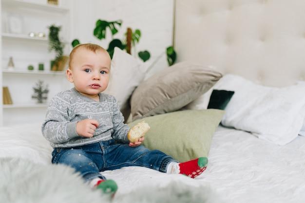 Netter kleiner kleinkindjunge, der auf bett sitzt und einen snack in seiner hand hält