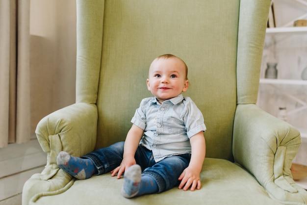 Netter kleiner kleinkindjunge, der im grünen sessel sitzt