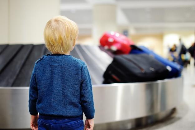 Netter kleiner müder kinderjunge am flughafen, reisend. umgekipptes kind, das mit kinderkoffer auf gepäckkarussell wartet.