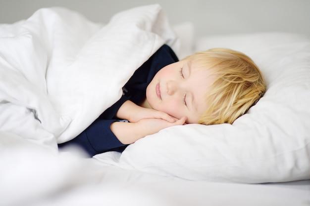 Netter kleiner schlafender junge. müdes kind, das im bett der eltern ein schläfchen hält.