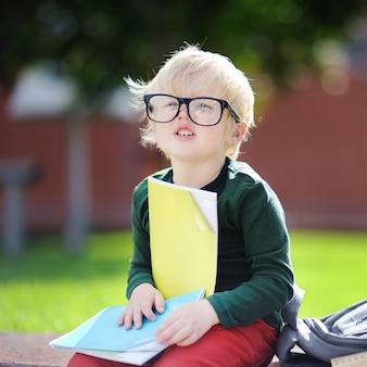 Netter kleiner schüler, der draußen am sonnigen tag studiert. zurück zum schulkonzept.