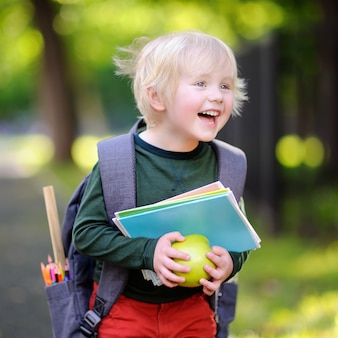 Netter kleiner schüler mit seinem rucksack und apfel. zurück zum schulkonzept.