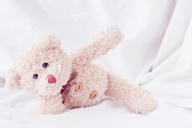 Netter kleiner teddybär legte sich auf das bett.