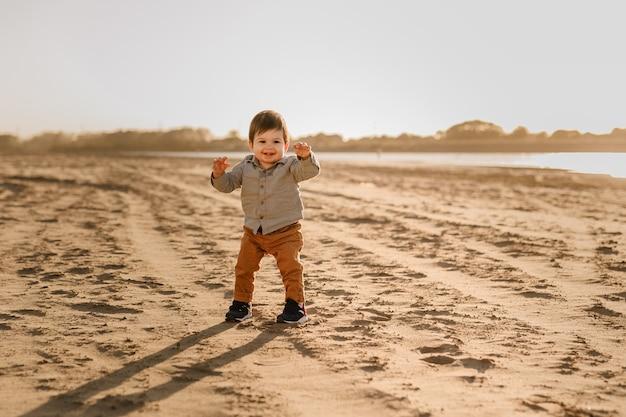 Netter kleinkindbabyjunge, der auf dem sandstrand geht.