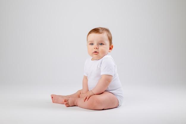 Netter kleinkindjunge 8 monate alt im weißen bodysuit sitzt