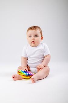 Netter kleinkindjunge 8 monate alt im weißen bodysuit spielt mit sich entwickelndem spielzeugsitzen