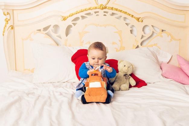 Netter kleinkindjunge, der auf dem bett sitzt und mit einem spielzeug spielt. frühes lernen für kinder. aktivitäten mit kindern zu hause.