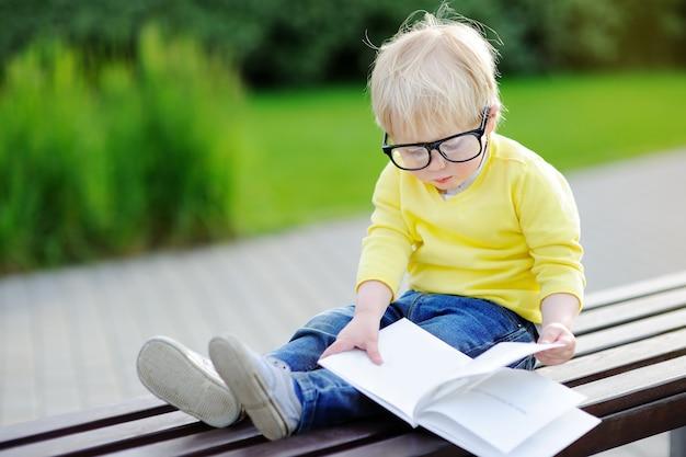 Netter kleinkindjunge, der draußen ein buch am warmen sommertag liest. zurück zum schulkonzept
