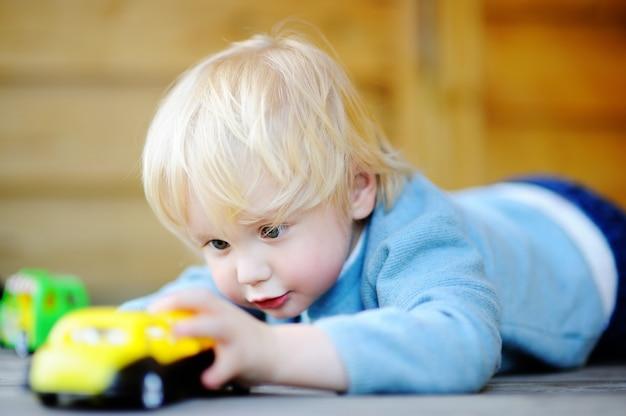 Netter kleinkindjunge, der draußen mit spielzeugautos am warmen sommertag spielt